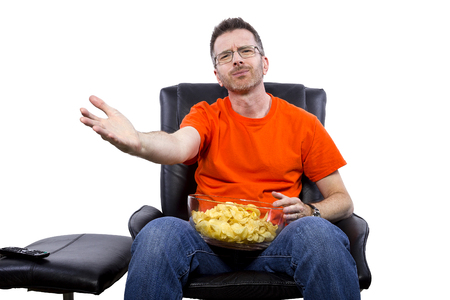 dissapointed: Front view of man watching TV while eating potato chips