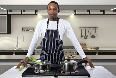 african american man: African American male chef wearing an apron in a home or restaurant kitchen