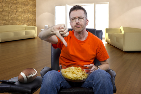 dissapointed: Front view of man watching football on TV with potato chip snacks