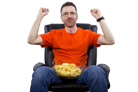 recliner: Front view of man watching TV while eating potato chips