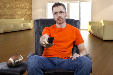 changing channel: Front view of male sitting in a living room watching football on tv