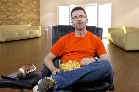 watching football: Front view of man watching football on TV with potato chip snacks