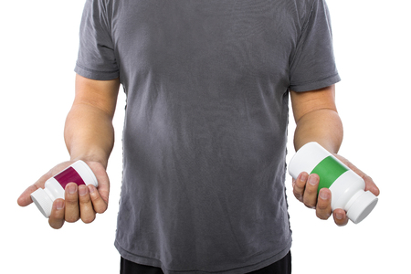 dietary supplements: Male comparing bottles of medicine or dietary supplements