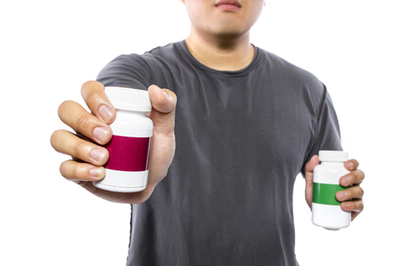 Male comparing bottles of medicine or dietary supplements