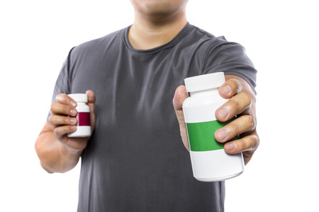 comparing: Male comparing bottles of medicine or dietary supplements