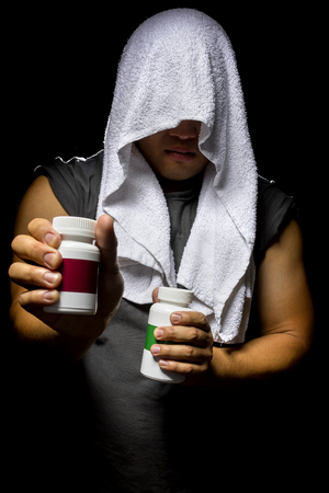 booster: Male athlete holding a bottle of energy booster supplements on a black background