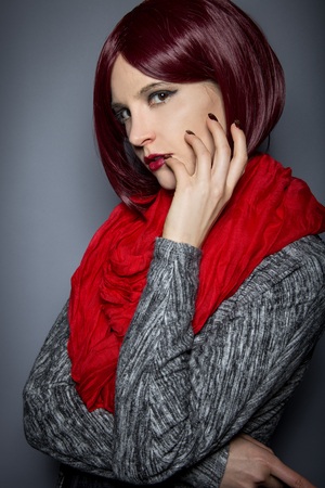 Woman with red hair and scarf showing nail polish art or manicure design