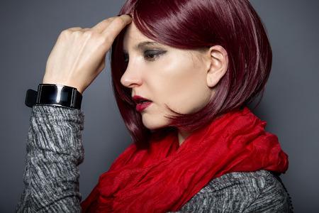 Stylish woman in red wearing an electronic smartwatch wearable tech