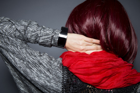 Stylish woman in red wearing an electronic smartwatch wearable tech