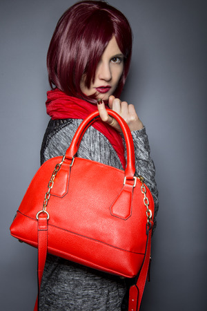 Woman dressed in spring or fall fashion holding a red purse or bag