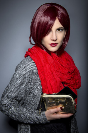 Redhead fashion model holding a stylish cell phone purse accessory