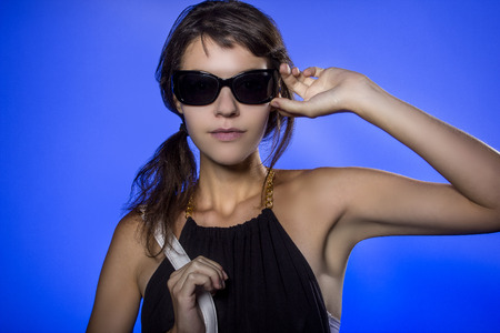 gels: Female teen wearing sunglasses on vivid background lit with blue color gels Stock Photo