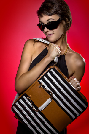 gels: Female holding a trendy leather purse on a background lit with red color gels