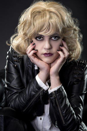 Female dressed in rebellious leather goth rocker style with black nail polish Banco de Imagens
