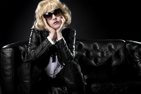 rockstar: Female in black leather and shades posing arrogantly like a famous rockstar Stock Photo