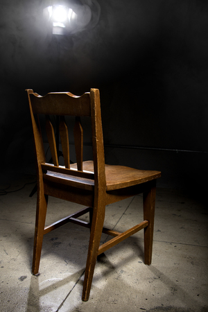 waiting convict: Isolated wooden chair in a dark scary prison with an interrogation spotlight