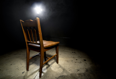 Isolated wooden chair in a dark scary prison with an interrogation spotlight