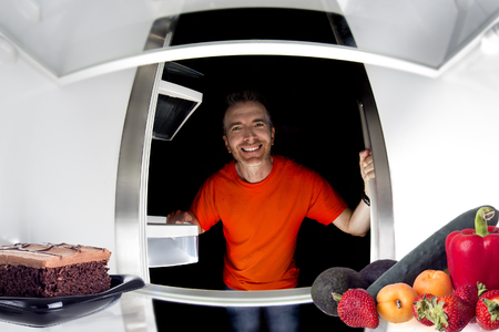 fridge: Hungry man looking in the fridge and choosing between cake or fruits and vegetables Stock Photo