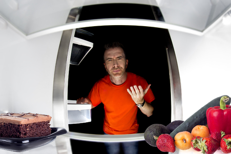 Hungry man looking in the fridge and choosing between cake or fruits and vegetables Imagens