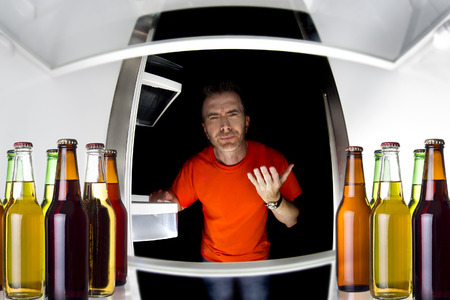 fridge: Man looking inside a fridge with bottles of beers late at night Stock Photo