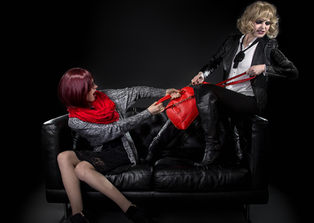 women fighting: Two jealous fashionable women fighting over red hand bag on a black couch Stock Photo