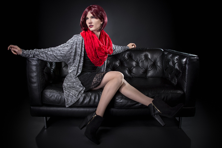 snob: Fashionable female sitting and resting on a comfortable black leather couch