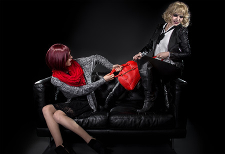 sibling rivalry: Two jealous fashionable women fighting over red hand bag on a black couch Stock Photo