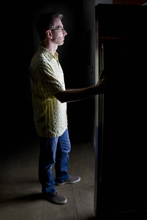 fridge: Man looking for food in an open fridge in a dark kitchen late at night