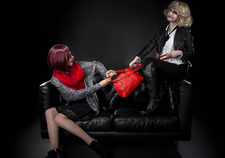 tugging: Two jealous fashionable women fighting over red hand bag on a black couch Stock Photo