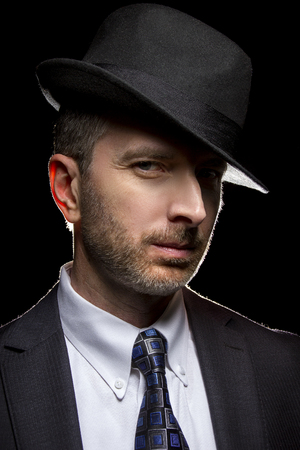 Man wearing a fedora hat as a film noir detective or gangster Stock Photo