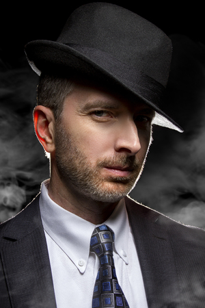 film noir: Man with a fedora hat posing as a film noir detective or gangster