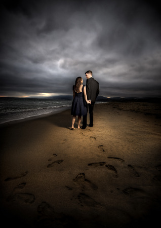 Loving engaged couple on honeymoon in a dramatic HDR beach island landscape Imagens