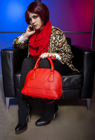 outgoing: Outgoing redhead female model with a red purse on a colorful background