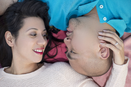 engaged: Engaged latino couple laying on a park looking carefree happy and in love