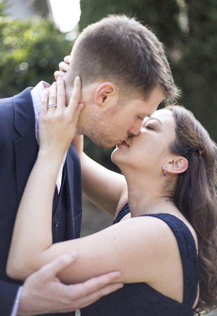 engaged: Close up of romantic engaged Caucasian and Asian couple kissing with engagement ring