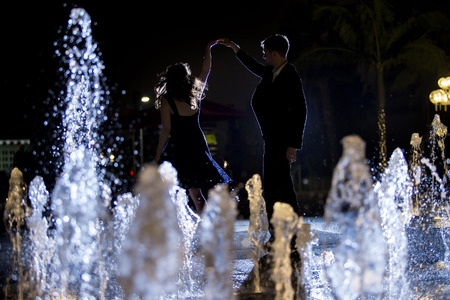 romantic date: Engaged interracial couple on a romantic date at night on a city fountain