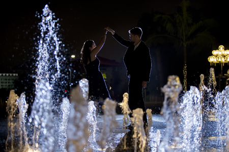 engaged: Engaged interracial couple on a romantic date at night on a city fountain