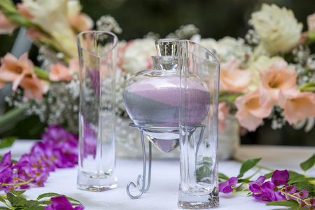 Sand ceremony vase in a wedding with colored sand being mixed together Stock Photo