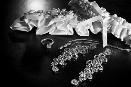 garter: Close up of wedding garter and bridal jewelry and engagement ring