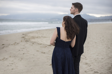 Engaged asian female and caucasian male in love in a romantic beach while wearing a dress and suit Standard-Bild