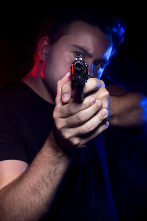 an assailant: Officer or criminal holding a gun lit with police lights Stock Photo