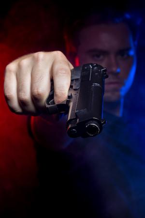 Cop disparar a un criminal o terrorista con pistola de humo iluminado por luces de la policía Foto de archivo - 61691399