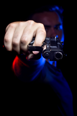 Funcionario o penal con una pistola iluminadas con luces de la policía Foto de archivo - 61691401