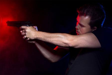 Cop disparar a un criminal o terrorista con pistola de humo iluminado por luces de la policía Foto de archivo - 61691405