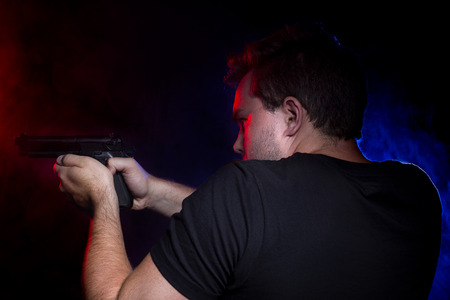 police lights: Cop shooting a criminal or terrorist with gun smoke lit by police lights