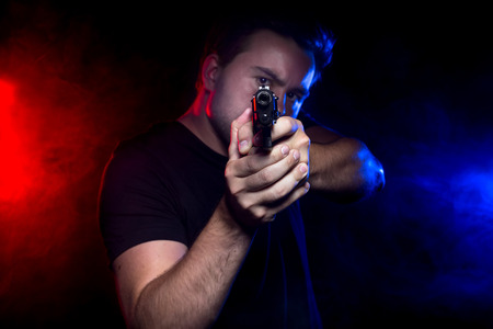 an assailant: Cop shooting a criminal or terrorist with gun smoke lit by police lights