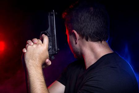Cop disparar a un criminal o terrorista con pistola de humo iluminado por luces de la policía Foto de archivo - 61691362