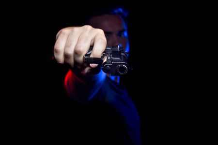 Funcionario o penal con una pistola iluminadas con luces de la policía Foto de archivo - 61691372