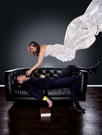 knocked out: Man dreaming on a couch of a girl in a wedding dress floating and descending to him