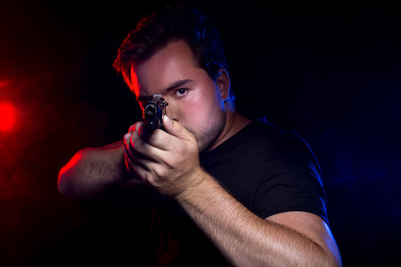 assailant: Officer or criminal holding a gun lit with police lights Stock Photo